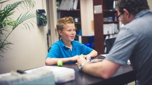 young boy smiles during his tutoring session to improve his executive functioning skills using applied behavior analysis in st. louis with Fit Learning 63141