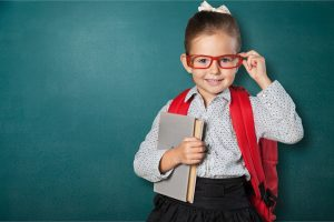 5 year old girl in glasses and a uniform meets with a preschool tutor and practices kindergarten readiness skills in St. Louis with Fit Learning 63141