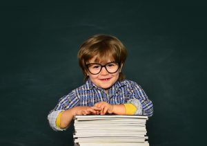 preschool aged boy with glasses leans on a stack of paper. He met with a preschool tutor in st. louis to improve his kindergarten readiness skills at Fit Learning