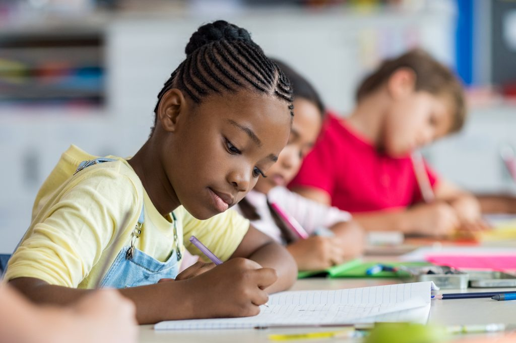 Girl writing next to classmates, she learns academic skills and gets help learning to focus with her attention deficit hyperactivity disorder in Creve Coeur, MO at Fit Learning St. Louis 63141
