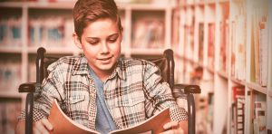 dyslexic child reads his book in a wheelchair in the library. He gets reading help and dyslexia tutoring at fit learning st. louis in creve coeur, mo 63141