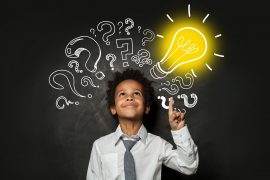 young boy next to question marks and a light bulb indicating the success of fit homeschool in St. Louis, MO at Fit Learning who offers tutoring in St. Louis, MO