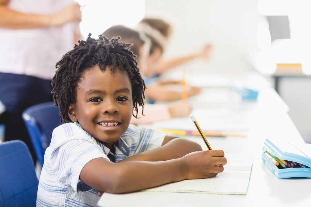 young boy smiles at the camera while writing on a piece of paper. He got penmanship help in St. Louis, MO when working with a tutor at Fit Learning St. Louis