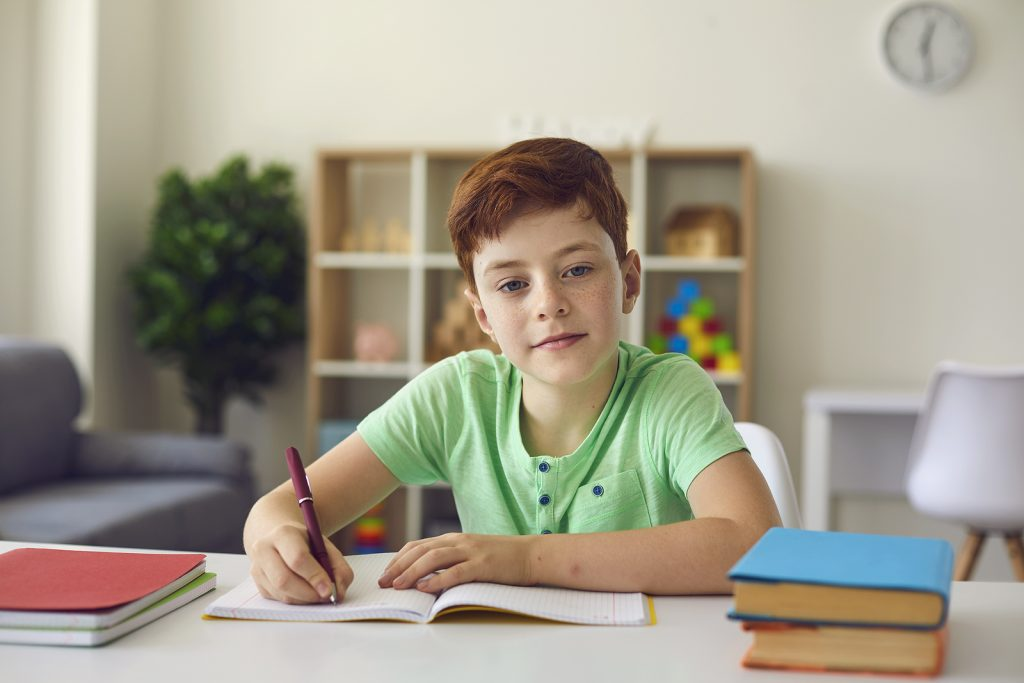 Cute red headed boy smiles while writing in a notebook at home. He gets penmanship help in St. Louis, MO from Fit Learning who provides tutoring in St. Louis, MO