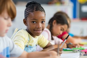 young african american girl looks at the camera and writes in her classroom. She feels confident after getting penmanship help in St. Louis at Fit Learning St. Louis 63141