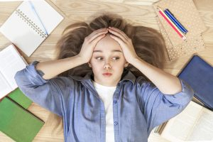 Stressed young girl next to a pile of school work and books. She gets homeschooling help and tutoring in St. Louis MO at Fit Learning St. Louis 63141