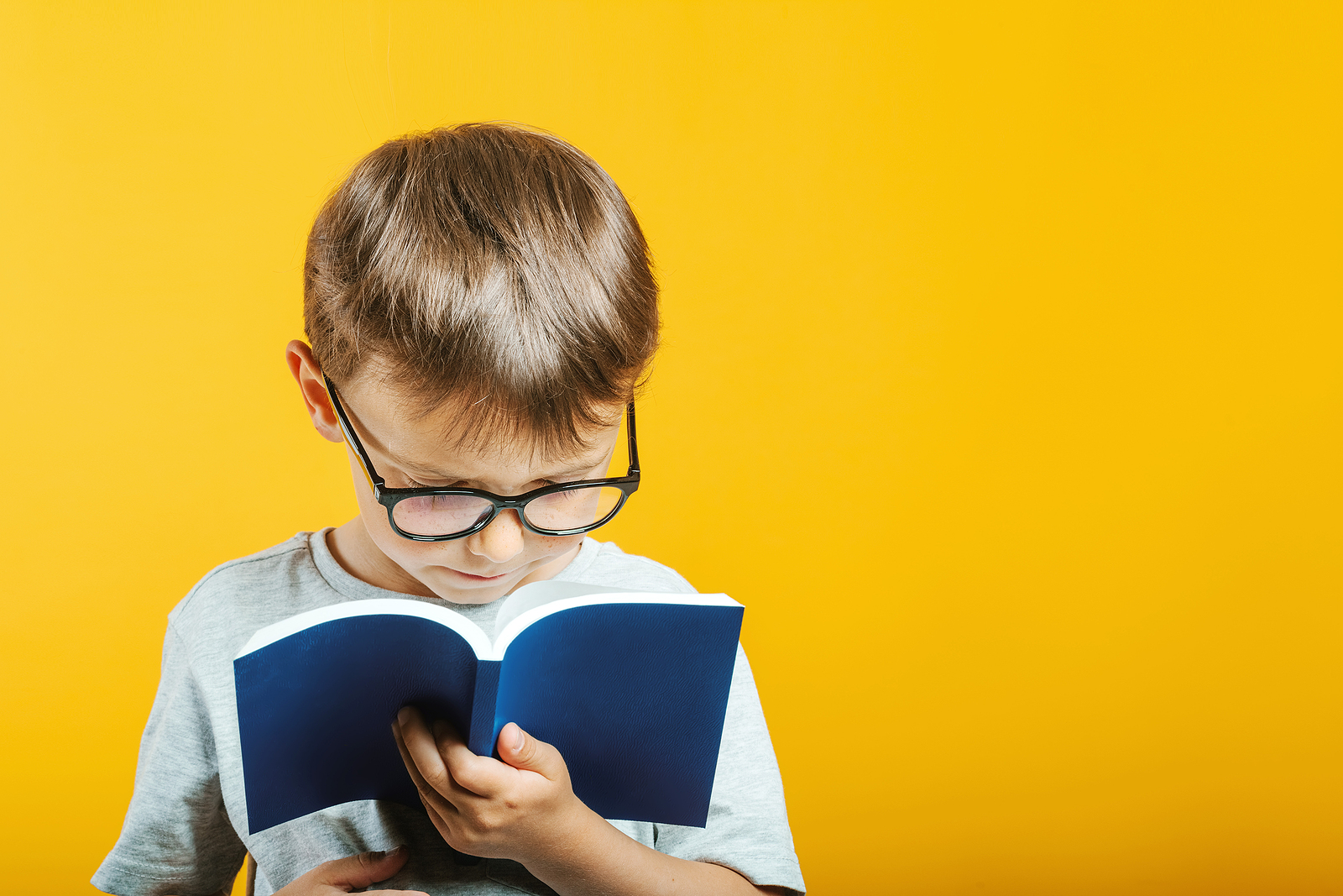 A child wearing glasses reads from their book with an interested look on their face. This could represent the effect Fit Tutoring has had on his reading ability. Contact Fit Learning for Fit Reading, Fit Tutoring, and other services. A private school tutor in St. Louis, MO who offers reading help may be the assistance your dyslexic child needs.