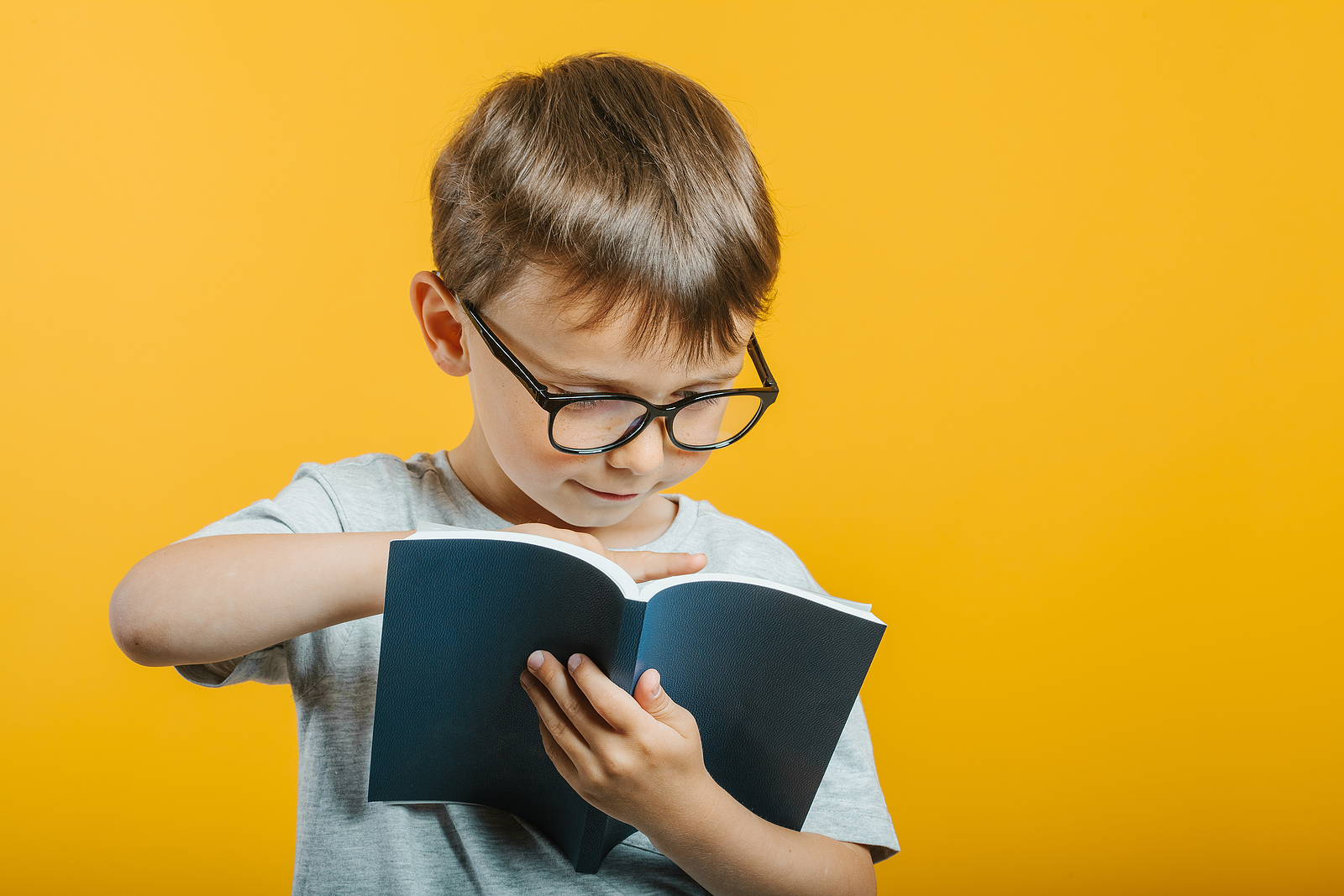 A child wearing glasses points to the page they are reading from their book. This could represent a curious student benefiting from Fit Reading. Contact Fit Learning for more info on finding the right private school tutor in St. Louis, MO to get reading help for your child