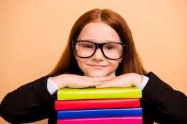 A happy student rests her head on a stack of books as she smiles. This could represent how tutoring in St. Louis, MO can support your child with online learning in St. Louis, MO and other services.