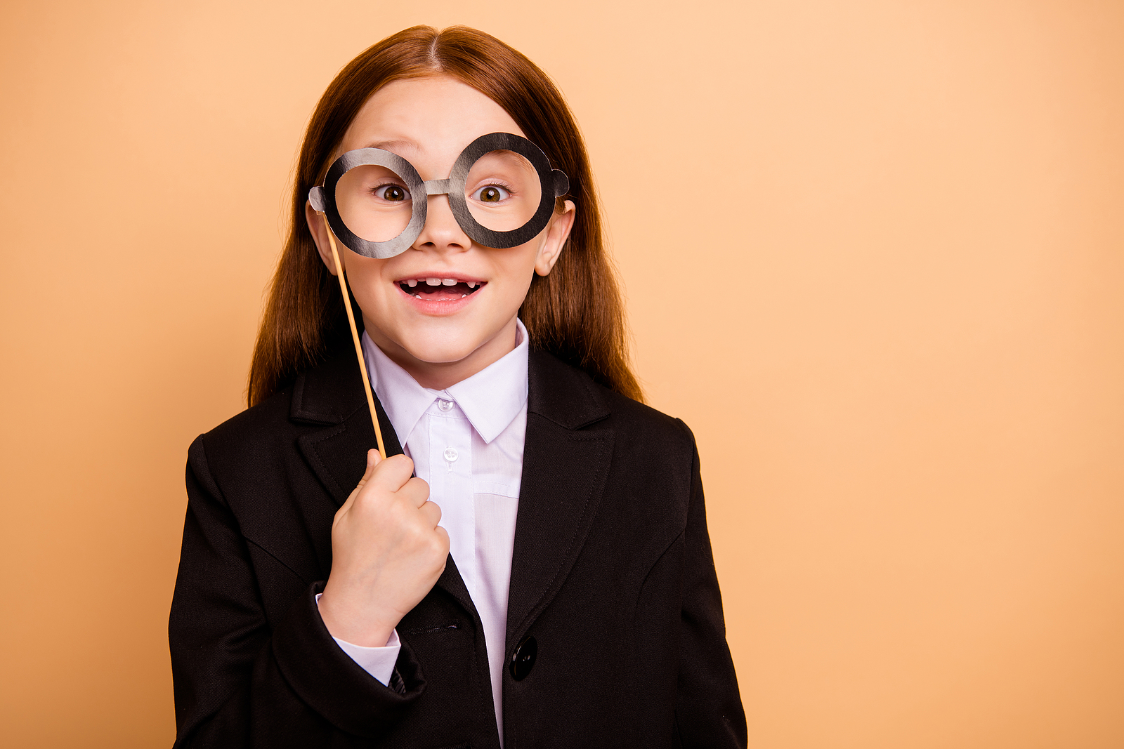 Excited young girl wearing a suit and a photo prop representing how Fit Learning makes Summer learning exciting & becomes an easy way to avoid Summer Brain Drain!