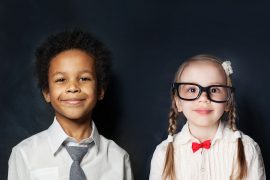 Two young children stand dressed as students, smiling. This could represent the joy that comes from Fit Learning in St. Louis, MO. We offer Fit Tutoring, private tutor support, and more. Contact a private school tutor in St. Louis, MO today to learn more.