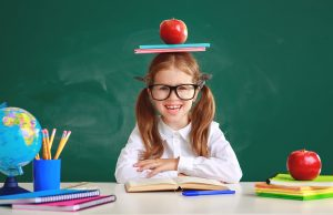 A young student stands at her desk while balancing an apple and stack of books on her head. This could represent a child benefiting from Fit Learning in St. Louis, MO. Contact us today to speak to a private tutor about Fit Tutoring.